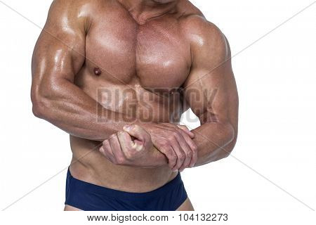 Midsection of shirtless man flexing muscles against white background