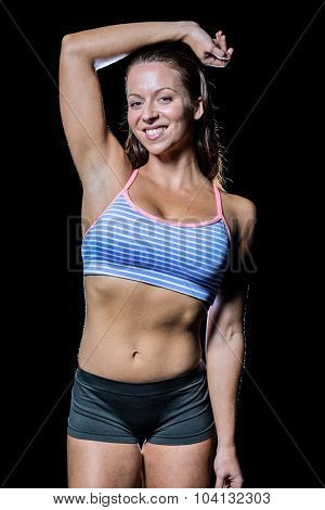 Portrait of happy female athlete with hand on head against black background