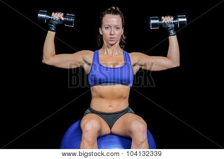 Portrait of woman lifting dumbbells while sitting on exercise ball against black background