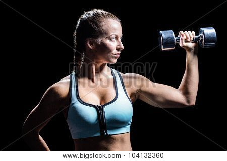 Fit woman lifting dumbbells against black background