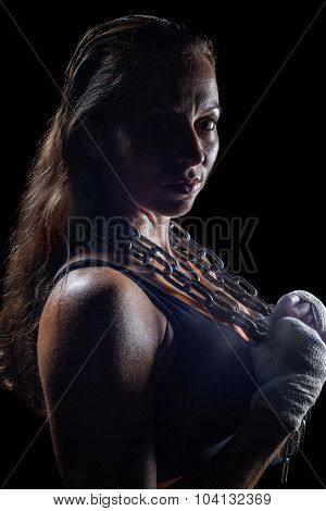 Portrait side view of female fighter holding chain against black background