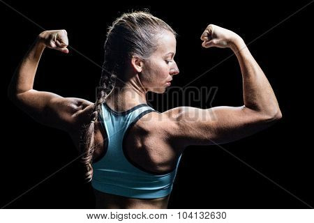 Athlete woman flexing muscles against black background