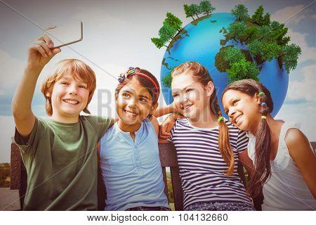 Happy children taking selfie at park against blue sky over fields