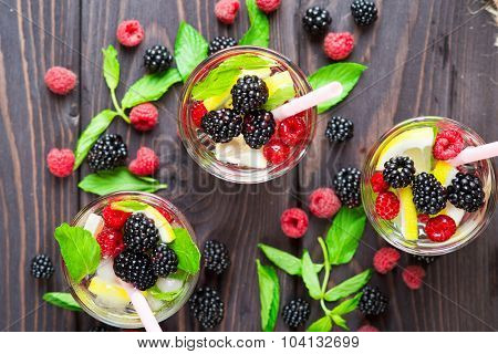 Cocktail with raspberry, blackberry, lemon and mint in glass on rustic wooden background