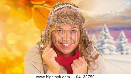 Happy blonde in winter clothes against autumn changing to winter