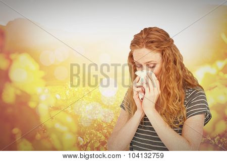 Sick blonde woman blowing her nose against autumn scene