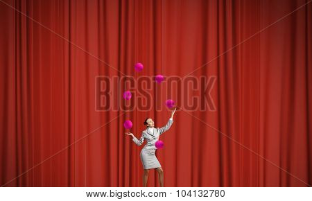 Young businesswoman in cap on stage juggling with balls