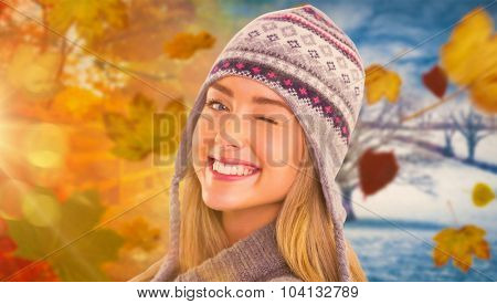 Happy blonde in winter clothes posing against autumn turning to winter