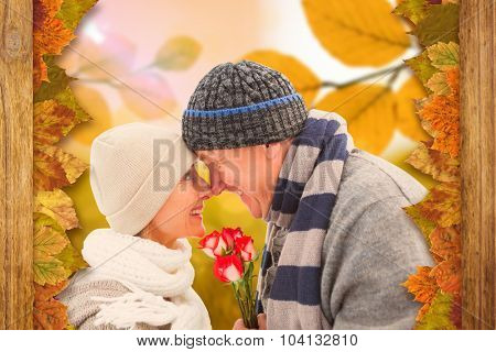 Happy mature couple in winter clothes with roses against autumn scene