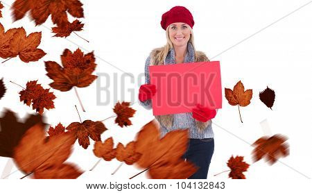Blonde in winter clothes holding red sign against autumn leaves