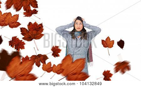 Anxious pretty brunette wearing winter clothes posing against autumn leaves