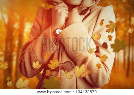 Attractive woman wearing a warm coat with hood raised against autumn scene