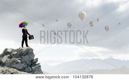 Businessman with umbrella and suitcase standing on mountain top