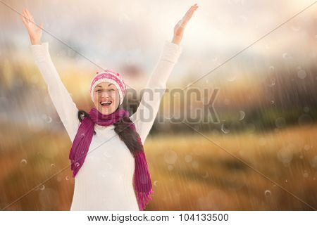 Pretty brunette in winter clothes against country scene