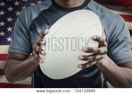 Mid section of sportsman holding rugby ball against close-up of american flag