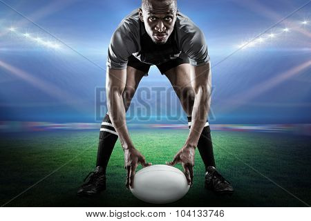 Sportsman holding ball while playing rugby against rugby stadium