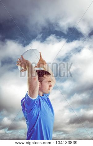 Disappointed rugby player holding his head against bright blue sky with clouds