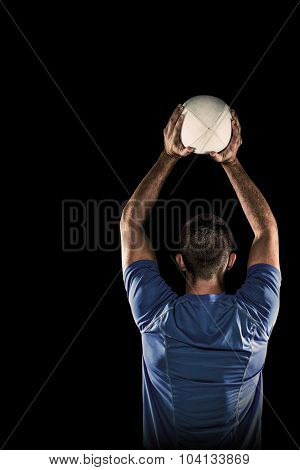 Rear view of sports player throwing ball against black