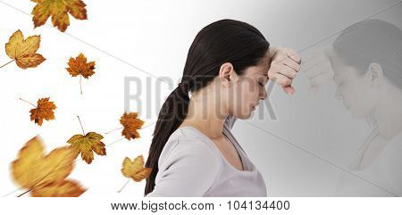 Sad woman leaning against the wall against autumn leaves pattern