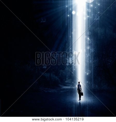 Rear view of businesswoman standing in light going from above
