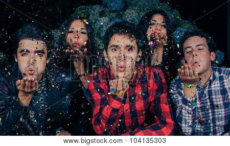 Friends group blowing confetti to the camera in a party