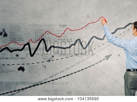 Back view of businessman drawing graphs on wall