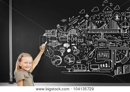 School girl writing chalk sketches on blackboard