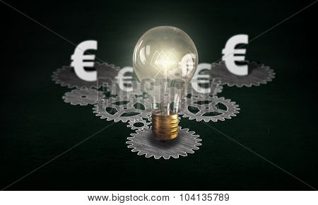 Gears mechanism and glowing light bulb on dark background
