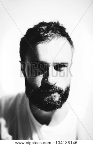 BW portrait of a bearded man wearing white tshirt on the light  background