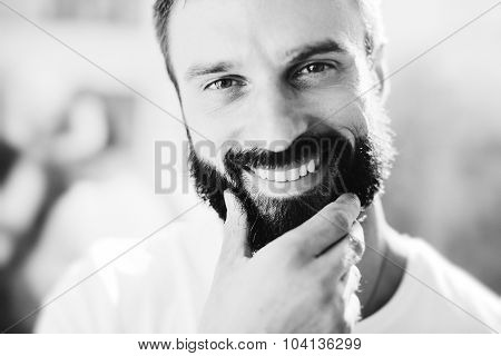 BW portrait of a bearded man wearing white tshirt and smiling
