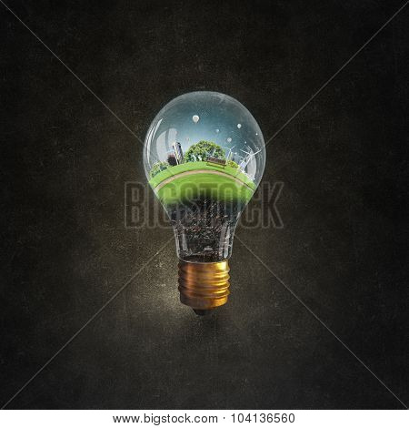 Think green concept with cityscape inside of light bulb