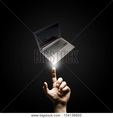 Male hand pointing with finger at laptop