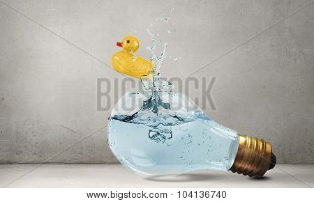 Glass light bulb and yellow rubber toy inside on blue background