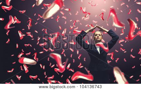 Young cheerful woman in suit and many falling shoes