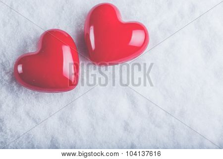 Two red glossy hearts on a frosty white snow winter background. Love and St. Valentine concept.