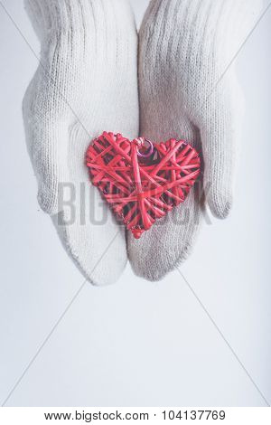 Female hands in white knitted mittens with a entwined vintage romantic red heart on a winter snow background. Love and St. Valentine cozy concept.