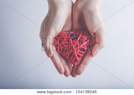 Female hands with a entwined vintage romantic red heart on a snow background. Love and St. Valentine concept.
