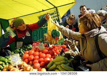 MOSCOW, RUSSIA - OCTOBER 04, 2015: Traditional Food Fair on the weekend. Vegetable stall, seller transfers to a customer with shopping bag.