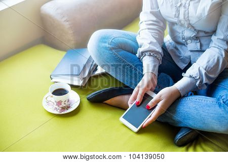Female With Smartphone And Coffee Cup Sitting At Home