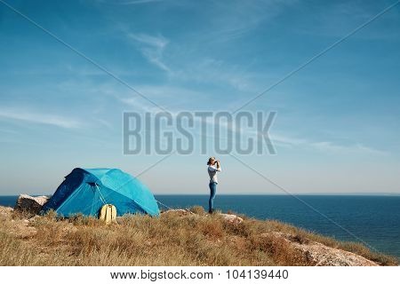 Hiker Looking In Binoculars Enjoying Spectacular View On Mountain Top Above The Clouds In National P