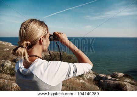 Young Beautiful Woman Hiker Looking Through Binocular On Mountain In Summer.