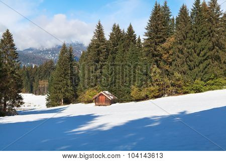 Wooden Hut In Winter Alpine Forest