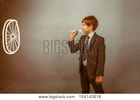 Teen boy businessman throwing darts at a target dart on a blue b