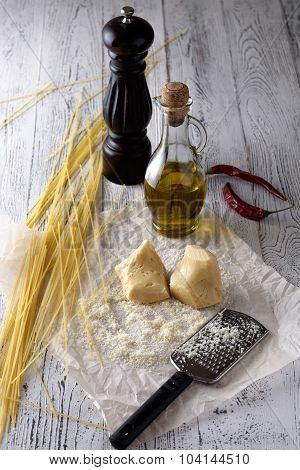 Grated Parmesan Cheese, Bottle Of Olive Oil And Metal Grater On Wooden Table