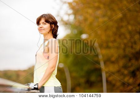 Young brunette woman with mp3 player doing fitness in city park