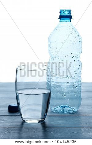 Empty Bottles And Glass Of Water On A Wooden Table.
