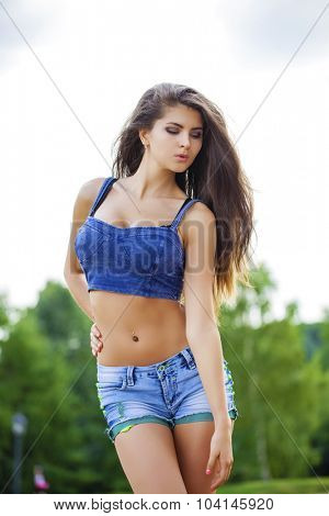 Close up portrait of young beautiful brunette woman in blue jeans short