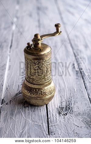 Vintage Still Life With Brass Pepper Mill Standing On The Wooden Background.