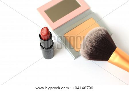 Lipstick and face powder isolated on white background