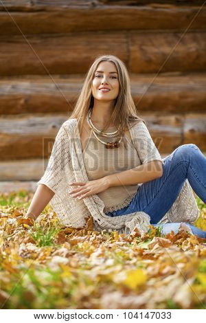 Young beautiful woman in blue jeans sitting in the autumn park